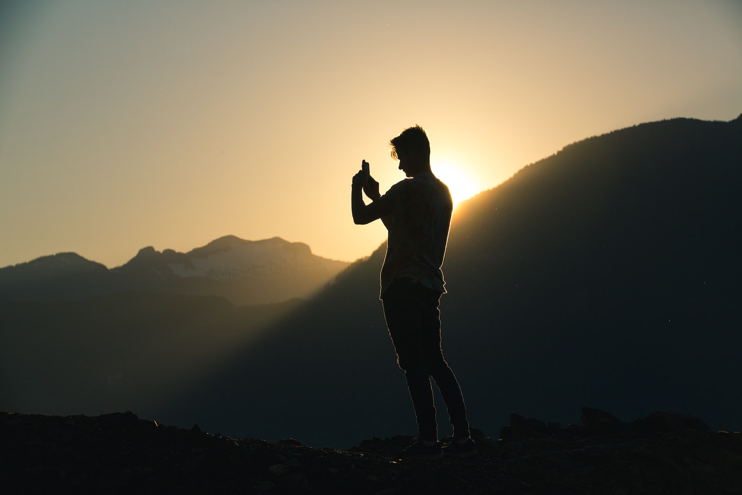 man on mountain taking a photo during golden hour