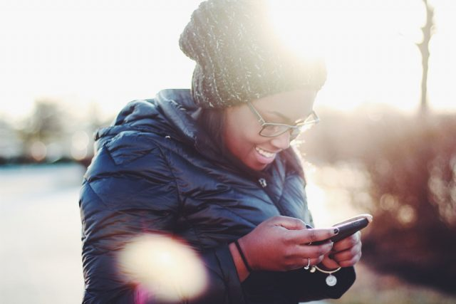 smiling person using phone
